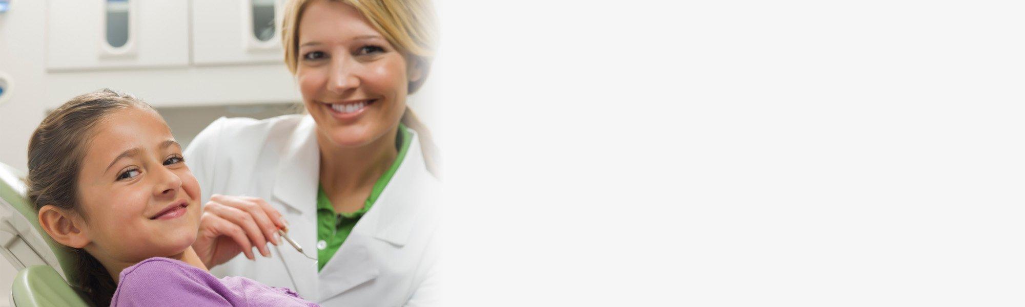 Une dentiste souriante assise à côté d'une filette