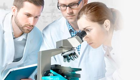 Female scientist looking through microscope with two male scientists beside her
